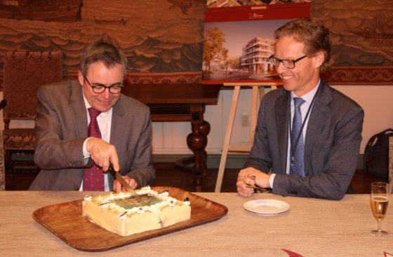 Burgemeester Jos Wienen snijdt de taart aan, Bemog-directeur Stefan van Dijk kijkt toe